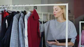 Young businesswoman is checking garments on rails and working with tablet in her clothing shop. She is checking prices. And labels, touching screen and typing stock footage