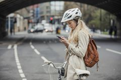 Checking Notifications on her Phone. Young businesswoman checking the notifications on her mobile phone while cycling to work Stock Image