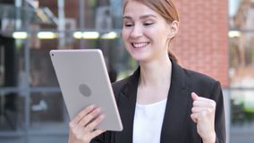 Young Businesswoman Cheering for Success on Tablet Outdoor