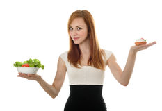 Young businesswoman choice lettuce salad or cake Stock Photo