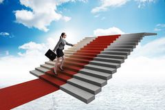 The young businesswoman climbing stairs and red carpet. Young businesswoman climbing stairs and red carpet Royalty Free Stock Photo