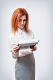 Young businesswoman with clipboard against white background Royalty Free Stock Images