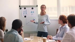 Young businesswoman coach drawing graph on flip chart give presentation. Young businesswoman coach presenter drawing graph on flip chart talking give stock video