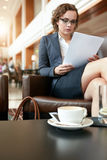 Young businesswoman in coffee shop reading documents Royalty Free Stock Photography
