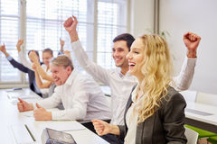 Young businesswoman and colleagues cheering Royalty Free Stock Image