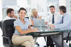 Young businesswoman with colleagues discussing in office Stock Photography