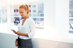 Young businesswoman concentrated writing text message on her mobile phone while standing in modern office interior, Royalty Free Stock Photos