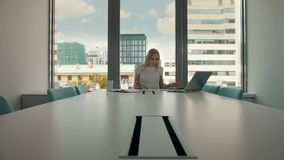 Young businesswoman in conference room with papers. Elegant blond woman sitting at long table in modern hall of office. Elegant blond woman sitting at long table stock video