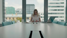 Young businesswoman in conference room with papers. Elegant blond woman sitting at long table in modern hall of office. Elegant blond woman sitting at long table stock video footage