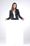Young businesswoman cover her lag with blank poster. Smiling and looking at the camera Stock Photo