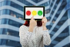 Customer service feedback. Young businesswoman covering her face using a digital tablet with three emoticons on the screen trying to choose one emotion face Royalty Free Stock Photos