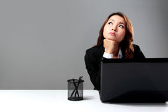 Young businesswoman  daydreaming in front of a laptop Stock Image