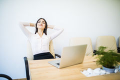 Young businesswoman is daydreaming in her office. Young beautiful businesswoman is relaxing at office Stock Photo