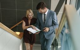 Business people walking up the steps and discussing. Young businesswoman discussing over a document with her colleague on stairs in the office building. Two Royalty Free Stock Image