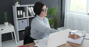 Businesswoman doing paperwork at office. Young businesswoman doing paperwork at office stock video footage