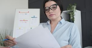 Businesswoman analyzing documents at office. Young businesswoman doing paperwork at office stock video