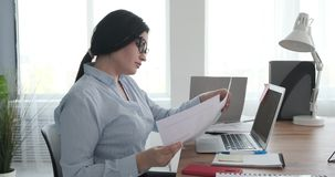 Businesswoman doing paperwork and using laptop at office. Young businesswoman doing paperwork and working on office laptop stock video footage