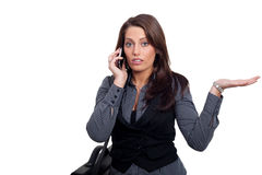 A young businesswoman in a dress is making a phone. A woman with a sellphone and a handcase, wearing a business look Stock Image