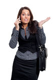 A young businesswoman in a dress is making a phone. A woman with a sellphone and a handcase, wearing a business look Stock Photography