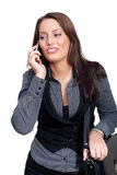 A young businesswoman in a dress is making a phone. A woman with a sellphone and a handcase, wearing a business look Royalty Free Stock Photography