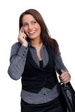 A young businesswoman in a dress is making a phone. A woman with a sellphone and a handcase, wearing a business look Royalty Free Stock Image