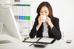 Young businesswoman drinking coffee in  office Royalty Free Stock Images