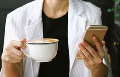 Young businesswoman drinking coffee and using smart phone in cafe, Business woman working on her coffee break in cafe bar Stock Photos