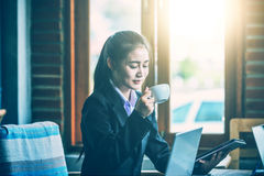 Young businesswoman drinking hot coffee during meeting Stock Photo
