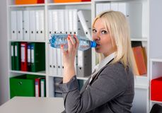 Young businesswoman is drinking water Royalty Free Stock Image