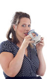 Young businesswoman drinks from mug. Young businesswoman drinks from a coffee mug; isolated on a white background Royalty Free Stock Photo