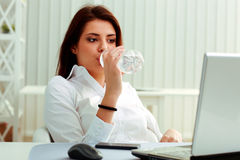 Young businesswoman drinks water on her workplace Royalty Free Stock Image