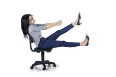Young businesswoman drives chair in studio Royalty Free Stock Images
