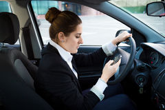 Young businesswoman driving a car and using phone Royalty Free Stock Photography