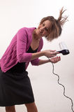 Young businesswoman drying her beautiful hair with hairdryer, ge Stock Images