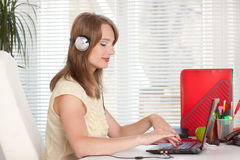 Young businesswoman in earphones at the office. Stock Photography