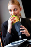 Young businesswoman eating a sandwich Royalty Free Stock Photos
