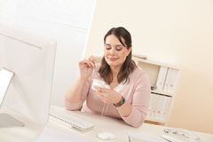 Young businesswoman eating yogurt at office Stock Photography