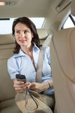 Young businesswoman with electronic organiser in car, smiling Royalty Free Stock Image