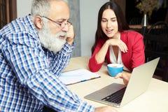 Young businesswoman explaining something to senior businessman Stock Image