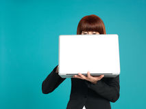 Young businesswoman, eyes showing behind laptop Royalty Free Stock Photos
