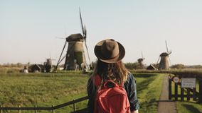 Young businesswoman feeling happy near a windmill. Successful female entrepreneur enjoys rustic mill farm scenery. 4K. Hands up. Excited and emotional. Success stock video
