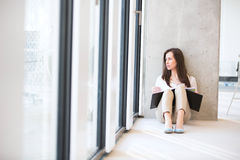 Young businesswoman with file looking through office window while sitting on floor royalty free stock photos