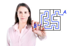 Young businesswoman finding the maze solution writing on the whiteboard. Stock Images