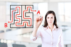 Young businesswoman finding the maze solution. Young businesswoman finding the maze solution writing on the whiteboard. Office background stock images