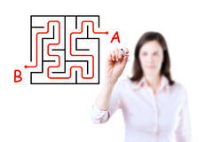 Young businesswoman finding the maze solution. Young businesswoman finding the maze solution writing on the whiteboard, white background royalty free stock photos