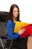 Young businesswoman with folders sitting in chair Royalty Free Stock Photo