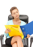 Young businesswoman with folders sitting in chair Royalty Free Stock Image