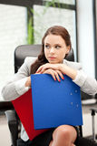 Young businesswoman with folders sitting in chair Royalty Free Stock Photography