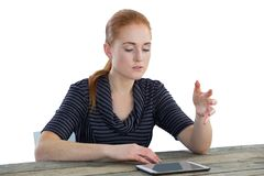 Young businesswoman gesturing over digital tablet. While sitting at table against white background Royalty Free Stock Photos