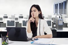Young businesswoman gesturing silence in the office. Young businesswoman gesturing silence with her forefinger over lips while working with a laptop in the Stock Image